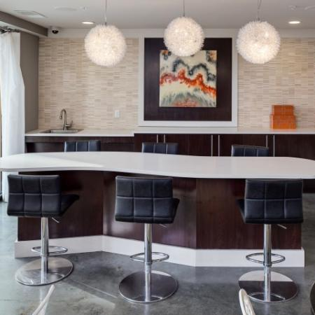 View of Resident Lounge, Showing Community Kitchen, Island, and Bar Stools at Cottonwood Westside Apartments