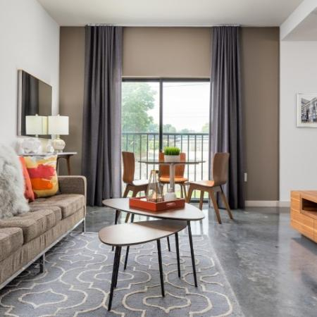 View of Living Room, Showing Furnished, Table, and View of Glass Sliding Doors at Cottonwood Westside Apartments