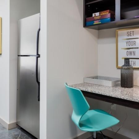 View of Kitchen, Showing Built-In Shelves and Desk and Stainless Steel Fridge at Cottonwood Westside Apartments