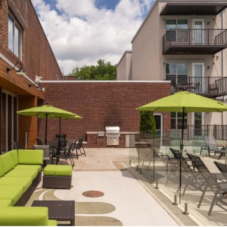 View of Outdoor Lounge, Showing Outdoor Furniture, Loungers, Picnic Areas, and Grill at The Melrose Apartments