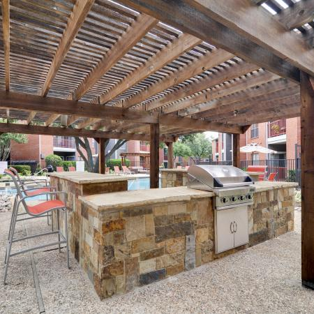 View of Grilling Lounge, Showing Grill, Serving Area, Chairs, and Pergola at 4804 Haverwood Apartments