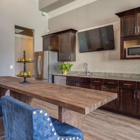 View of Resident Lounge, Showing Community Kitchen, Granite Countertop, Long Table, and TV at Arbors at Fairview Apartments