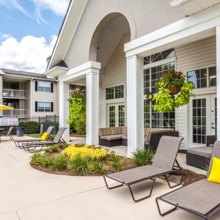View of Pool Area, Showing Loungers, Chair, Table, Umbrella, and Adjacent to Resident Lounge at Arbors at Fairview Apartments