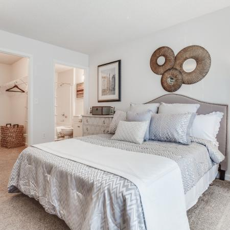 View of Classic Apartment Interior, Showing Bedroom With Bedding, View of Closet, and Bathroom at Arbors at Fairview Apartments