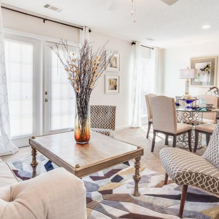 View of Classic Apartment Interior, Showing Furnished Living Room With Sitting Area and View of Dining Area at Arbors at Fairview Apartments