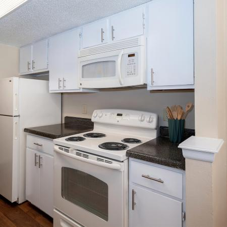 View of Classic Apartment Interior, Showing Kitchen With Electric Appliances, Cabinets, Plank Flooring at Blue Swan Apartments