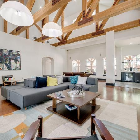 View of Clubhouse, Showing Tall Ceilings With Wooden Beams, Seating, and Décor at Bluffs at Vista Ridge Apartments