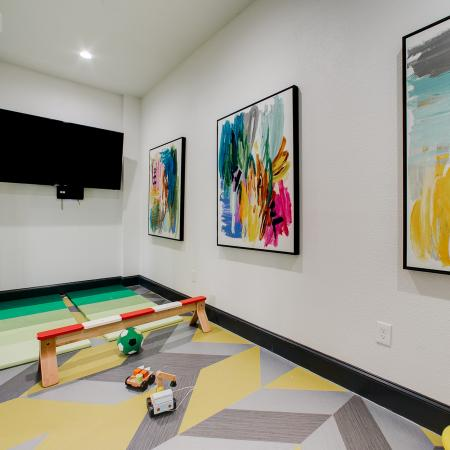 View of Children's Playroom, Showing Décor, Activities, and Flat Screen TV at Bluffs at Vista Ridge Apartments