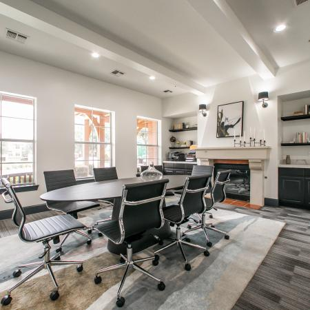 View of Conference Space, Showing Table and 6 Chairs, Fireplace, Built-In Bookcase and Windows at Bluffs at Vista Ridge Apartments