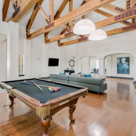 View of Billiards Room, Showing Tall Ceilings With Wooden Beams, Pool Table, and Seating at Bluffs at Vista Ridge Apartments