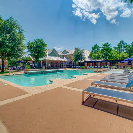 View of Resort Style Pool, Showing Sundeck, Loungers, and Umbrellas On A Sunny Day at Bluffs at Vista Ridge Apartments