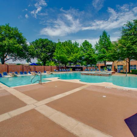 View of Resort Style Pool, Showing Loungers, Trees, Sundeck, and Clubhouse Exterior at Bluffs at Vista Ridge Apartments