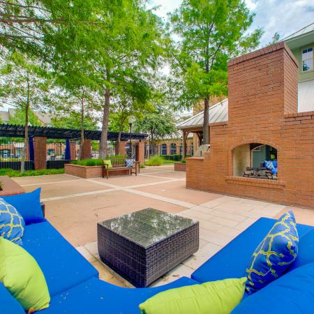 View of Outdoor Lounge, Showing Seating, Table, Landscaping, and Brick Fire Place at Bluffs at Vista Ridge Apartments
