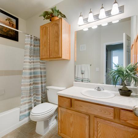 View of Classic Apartment Interior, Showing Furnished Bathroom With Single Vanity, Oversized Tub, and Tile Floor at Bluffs at Vista Ridge Apartments