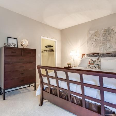 View of Classic Apartment Interior, Showing Bedroom with Layered Bedding, and View of Closet at Waterford Creek Apartments