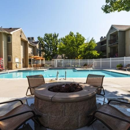 View of Pool Area, Showing Firepit with Chairs, Fenced-In Area, and Apartment Buildings in Background at Cottonwood Apartments