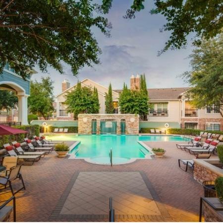 Image off cottonwood ridgeview pool facing the water fall feature and showing pool chairs and umbrellas