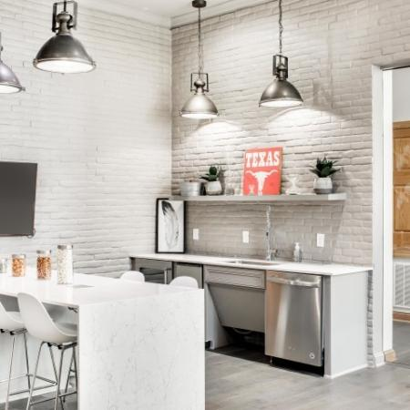 Image of Cottonwood Ridgeview's community kitchen with counter, 4 white counter stools, mini fridge and flat screen tv