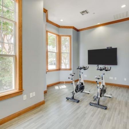 Image of spin bikes with fitness on demand tv monitor in front of them