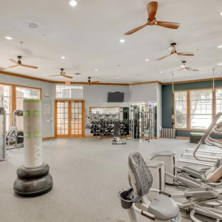 Image of private fitness center with cardio machines, free weights, and cable machines
