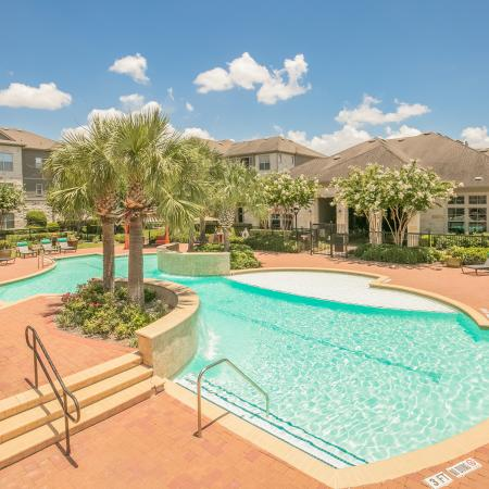 View of Resort Style Pool, Showing Sundeck, Loungers, and Building Exteriors on a Sunny Day at Retreat at Stafford Apartments