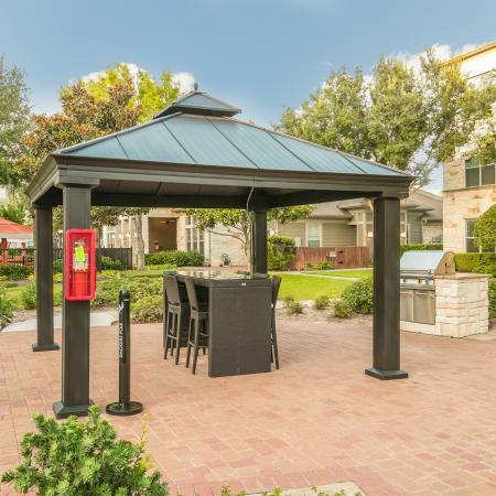 View of Outdoor Pavilion, Showing Covered Table and Chairs, Gas Grill, and Landscaping at Retreat at Stafford Apartments