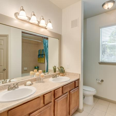 View of Bathroom, Showing Double Vanity, Large Mirror, Toilet, Tile Flooring and Window at Retreat at Stafford Apartments