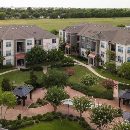 View of Building Exterior, Showing Aerial of Common Greenspace and Outdoor Pavilions at Retreat at Stafford Apartments
