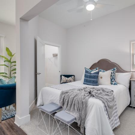 View of Bedroom, Showing Layered Bedding, Ceiling Fan, and View of Living Room at The Melrose Apartments