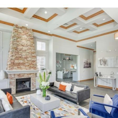Image of Cottonwood Ridgevew's resident clubhouse with grey couches, blue accent chairs, and a fireplace