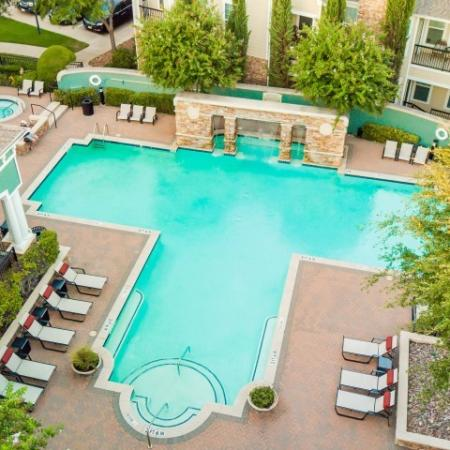 Aerial view of cottonwood ridgeview pool showing step in entry, lounge chairs, hot tub and waterfall feature