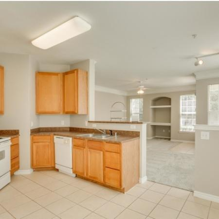 Image of classic style apartment kitchen with white appliances and oak cabinetry looking into the living room