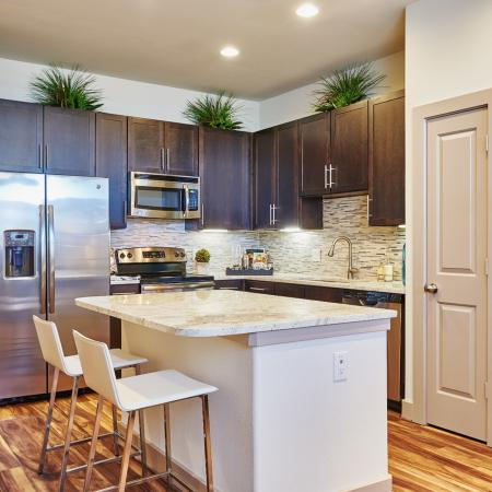 View of Kitchen, Showing Granite Counter Top, Island, and Plank Wood Flooring at 3800 Main Apartments