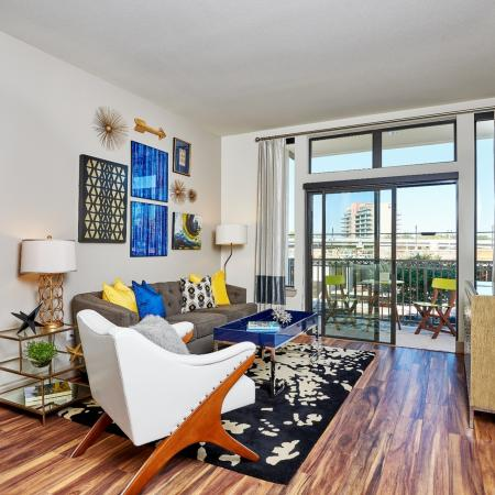 View of Living Room, Showing Plank Wood Flooring and View of Balcony at 3800 Main Apartments