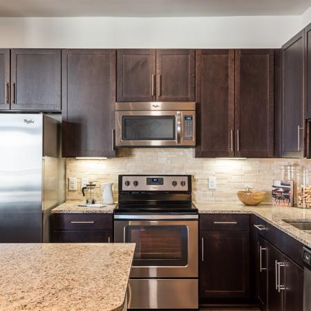 Brand new kitchen featuring stainless steel appliances, granite countertops, and espresso top and bottom cabinets.