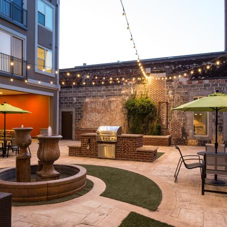 View of Outdoor Lounge, Showing Grill, Picnic Areas, and Fountain at The Melrose Apartments