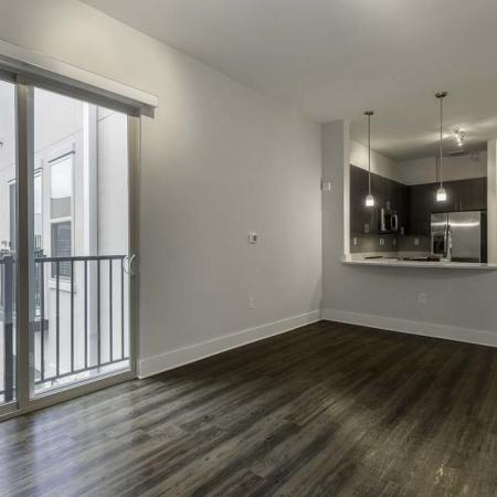 View of Living Room, Showing Plank Wood Flooring, Sliding Glass Door, and View of Kitchen at The Melrose Apartments