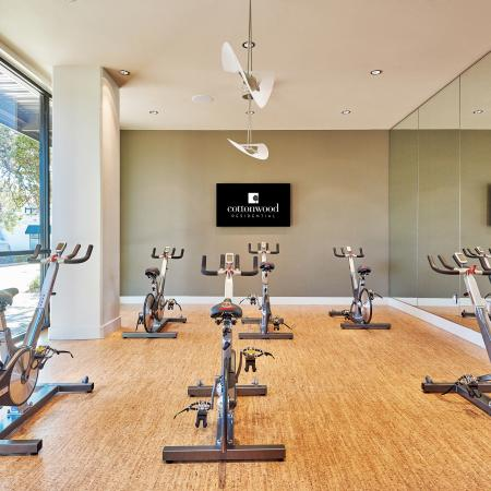 Fitness center equipped with stationary bikes, large wall-mount flat screen TV, and floor  to ceiling mirrors.