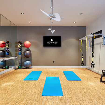 Fitness center equipped with yoga mats, exercise balls, resistance bands, free weights, floor-to-ceiling mirrors and a large  wall-mount flat screen TV.