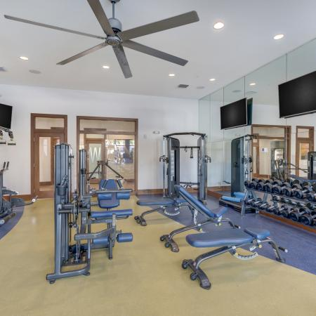 Image of free weights, cable machines and flat screen tvs in The Marq's fitness center