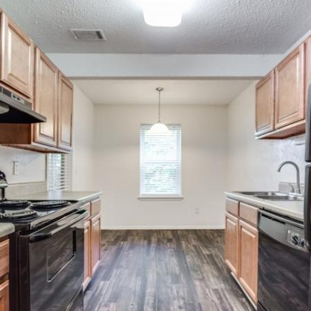 View of Classic Apartment Interior, Showing Kitchen with Plank Wood Flooring, Cabinets, Black Appliances at Plantations at Haywood Apartments
