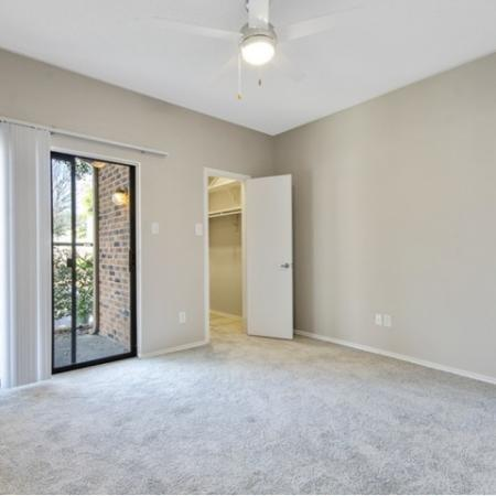 View of Renovated Apartment Interior, Showing Bedroom with Carpet, Ceiling Fan, and Sliding Glass Door to Patio at Spring Pointe Apartments