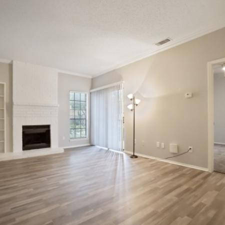 View of Renovated Apartment Interior, Showing Living Room with Plank Wood Flooring and Fireplace at The Oaks of North Dallas Apartments