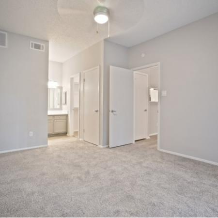 View of Renovated Apartment Interior, Showing Bedroom with Ceiling Fan and View of Bathroom at The Oaks of North Dallas Apartments