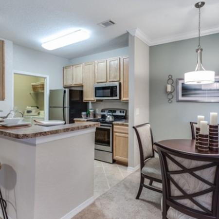 View of Classic Apartment Interiors, Showing Dining Room With Table, Open Galley Kitchen, and Laundry Room at Cottonwood Reserve Apartments