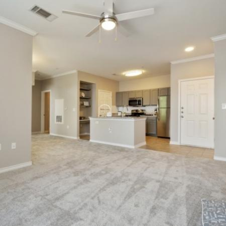 View of Renovated Apartment Interior, Showing Living Room With Ceiling Fan, Entrance, and Adjacent Kitchen at Bluffs at Vista Ridge Apartments