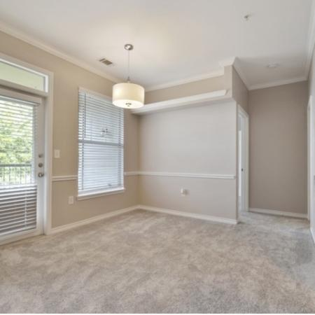 View of Renovated Apartment Interior, Showing Dining Room With Carpet and Door to Private Patio or Balcony at Bluffs at Vista Ridge Apartments