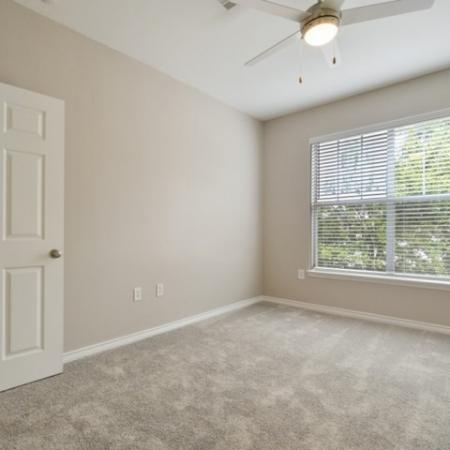 View of Renovated Apartment Interior, Showing Bedroom With Carpet, Ceiling Fan, and Large Window at Bluffs at Vista Ridge Apartments