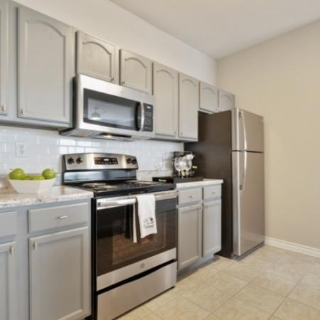 View of Renovated Apartment Interior, Showing Kitchen With Electric Appliances, Cabinetry, and Tile Flooring at Bluffs at Vista Ridge Apartments