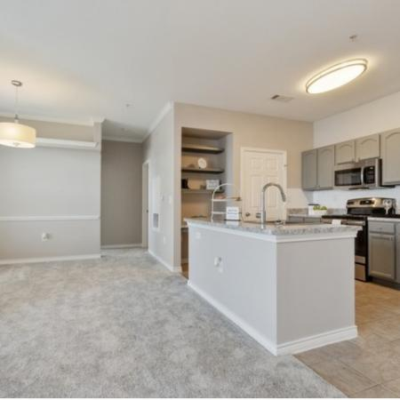 View of Renovated Apartment Interior, Showing Kitchen With Electric Appliances, Island, and Tile Flooring at Bluffs at Vista Ridge Apartments